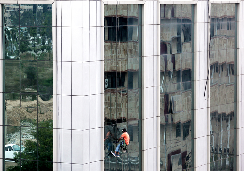 A worker cleaning mirrors of a building at Bahu Plaza, Jammu. -Excelsior/Rakesh