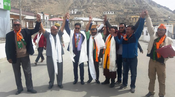 Union MoS Home Kiren Rijiju, BJP leader Avinash Rai Khanna and CEC Jamyang Tsering Namgayal raise hands after filing nomination papers in Leh on Tuesday. —Excelsior/Morup Stanzin