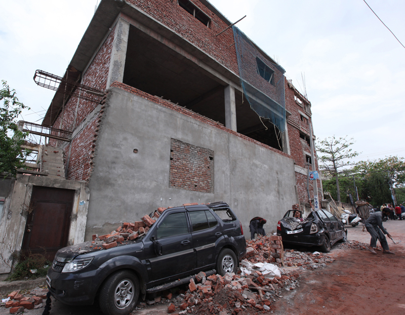 Two vehicles damaged due to fall of a building wall during windstorm in Jammu on Tuesday night. —Excelsior/Rakesh