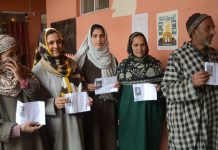 Voters show their cards while queuing up for their turn outside a polling booth in Budgam. — Excelsior/Shakeel