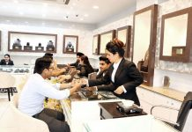 Customers selecting items at 'Zevar' jewellery showroom in Gandhi Nagar.