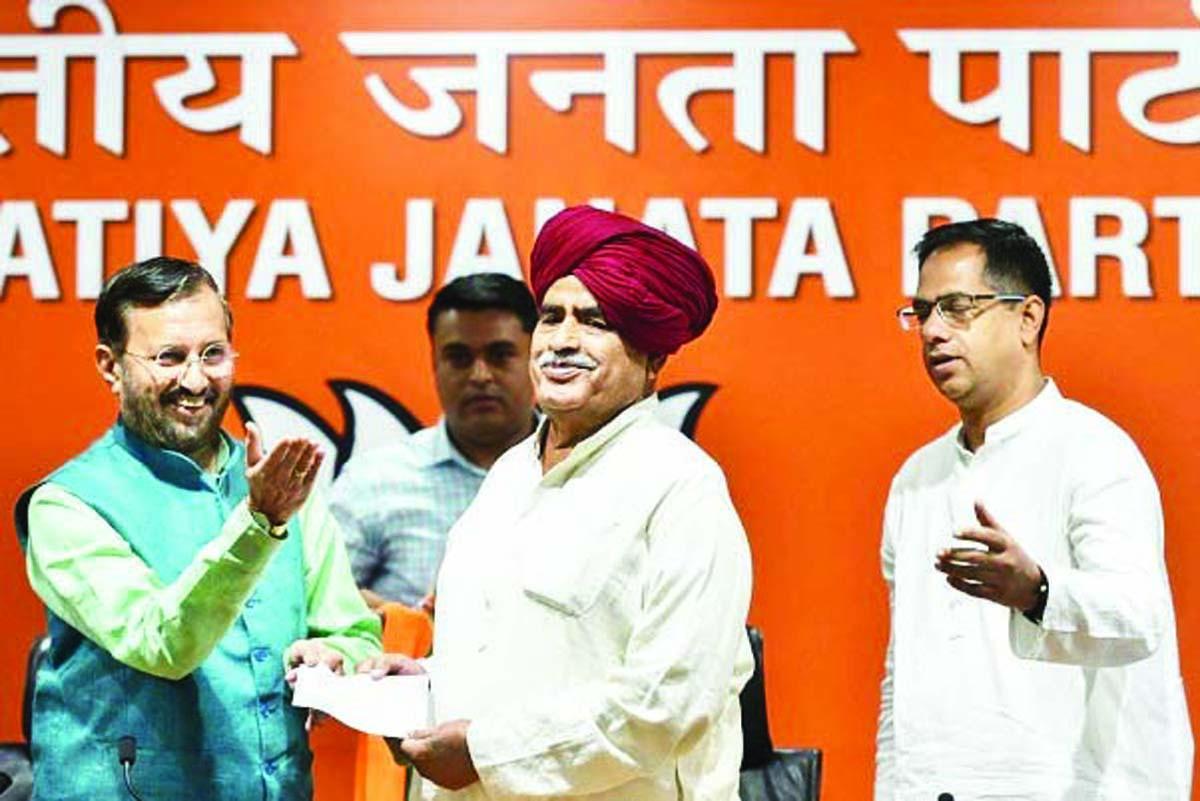 Union Minister and BJP leader Prakash Javadekar presents the membership slip to Gurjar leader Kirori Singh Bainsla, as he joins BJP, ahead of Lok Sabha polls, in New Delhi.