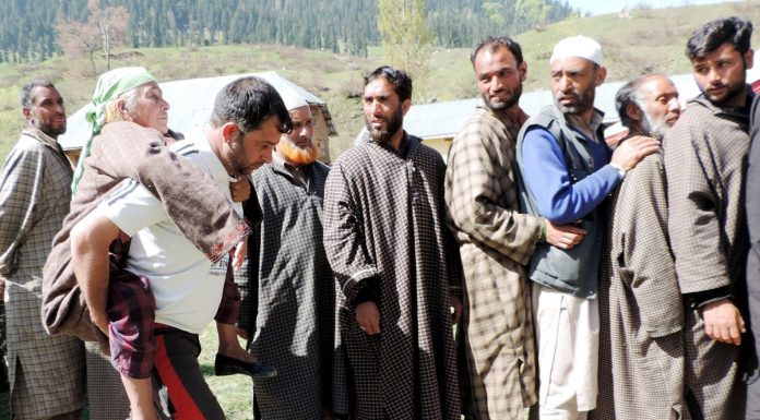 A man carrying his mother on shoulders to cast her vote at a polling station in Gulzarpur, Kulgam as people wait in queue for exercising their right to franchise on Monday. (UNI).