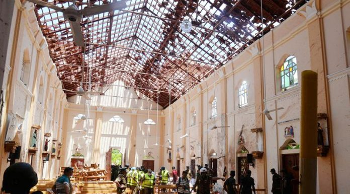 Crime scene officials inspect the site of a bomb blast inside a Church in Negombo, Sri Lanka on Sunday.