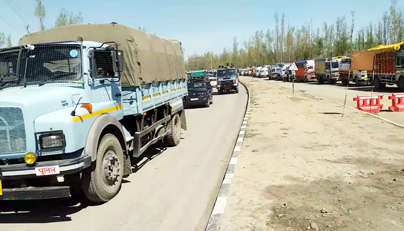 Security convoy moves on National Highway (left) while civil trucks remained stranded (right) near National Highway on Sunday. -Excelsior/Sajad Dar