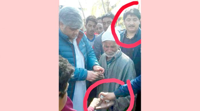 NC workers allegedly giving away money to people to lure voters in Sonawari Sumbal. Son of NC candidate Mohammad Akbar Lone (encircled) can be seen in the photograph.