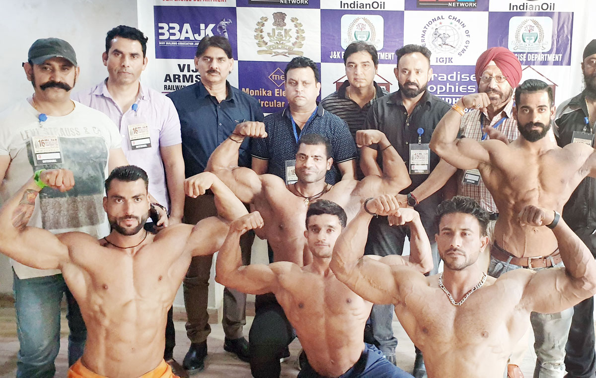 Bodybuilders displaying muscles during weighing process at International The Gym in Jammu.