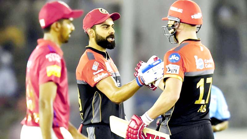 RCB skipper Virat Kohli and his teammate AB de Villiers celebrating during a big partnership before their victory against Kings XI Punjab.