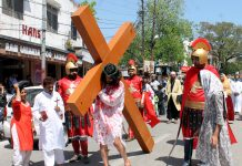 A believer carrying wooden cross depicting crucifixion of Jesus Christ during a procession on the occasion of Good Friday at Jammu. -Excelsior/Rakesh