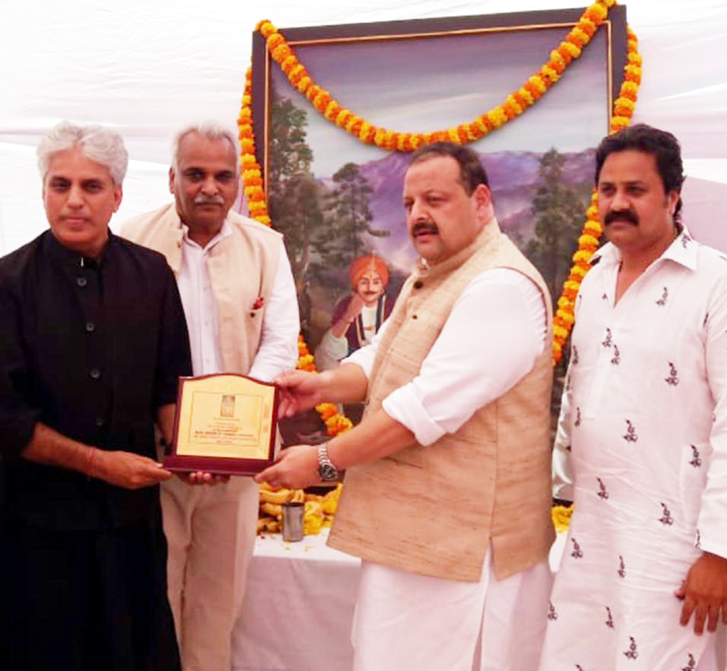 Ex-MLA Devender Rana and MLC Ramesh Arora presenting a memento to artist K K Gandhi during birth anniversary celebration of Mian Dido at Jagti on Sunday.