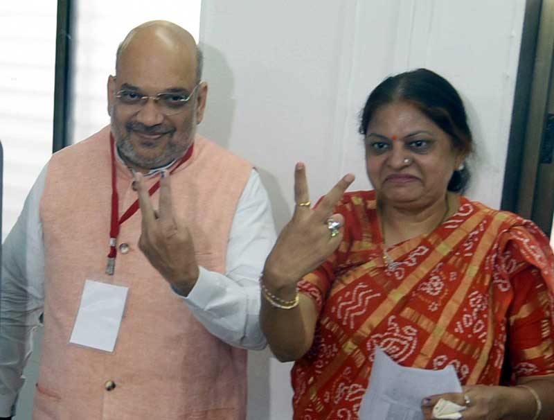 BJP National President Amit Shah and his wife showing their inked fingers after casting votes at a polling station, in Ahmedabad on Tuesday. (UNI)