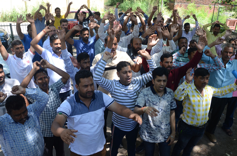 PHE workers staging protest near Press Club in Jammu on Monday. - Excelsior/Rakesh