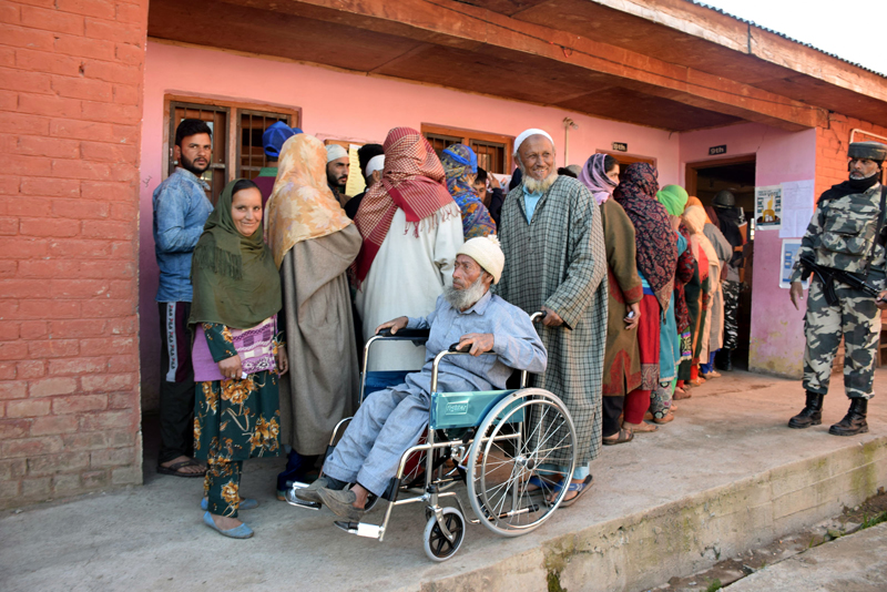 An elderly person returns on a wheel-chair after casting vote as other people wait for their turn to exercise their right to franchise in Shopian on Monday. -Excelsior/Younis Khaliq