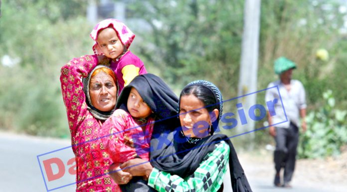 Women shield children from the Sun using their scarf and hankerchief during a hot summer day in Jammu on Monday. -Excelsior/Rakesh