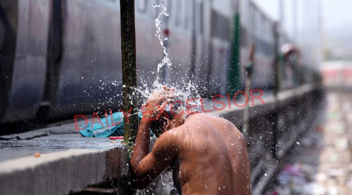 A man takes bath at Railway Station to cool himself on a hot summer afternoon in Jammu on Wednesday. —Excelsior/Rakesh