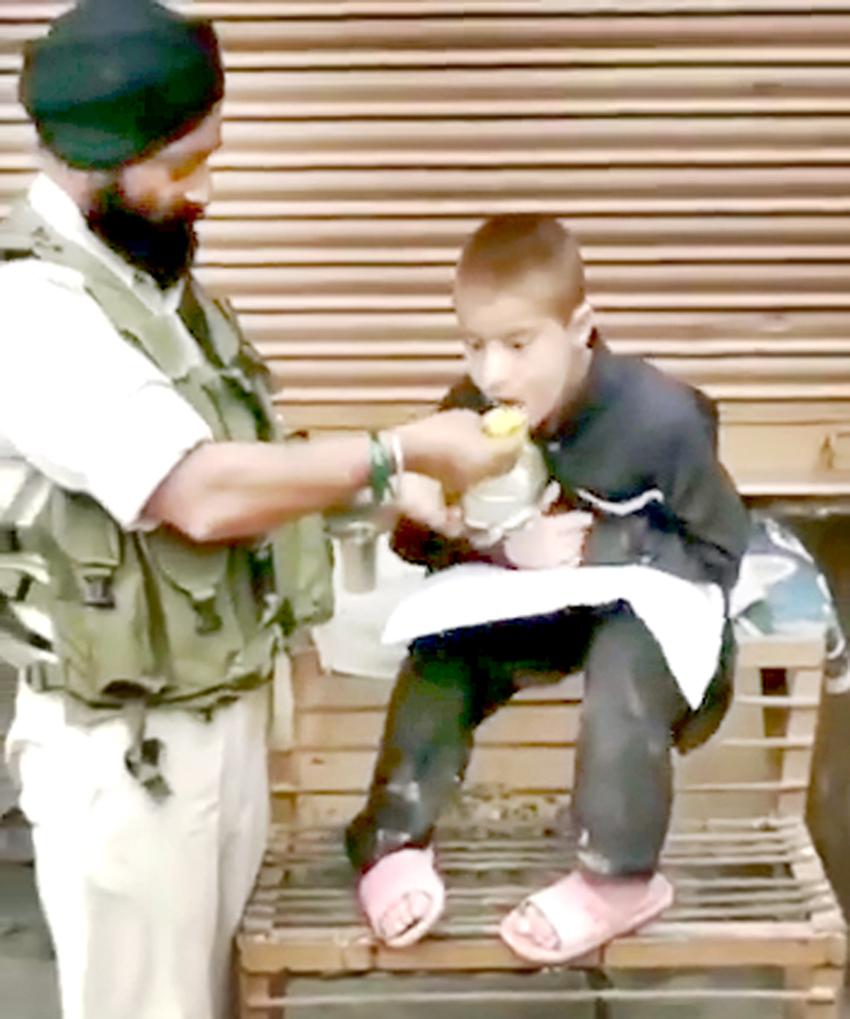 CRPF cop feeding the boy.