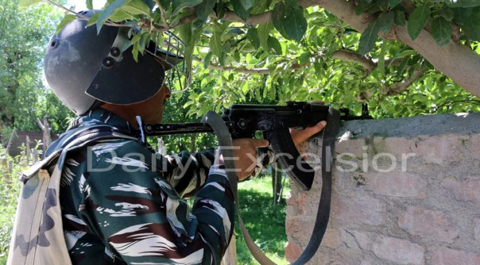 An Army jawan takes position during encounter at Dangerpora, Sopore on Thursday. -Excelsior/Aabid Nabi