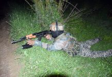 An Army jawan takes position at the site of encounter in Tral on Thursday evening. —Excelsior/Younis Khaliq