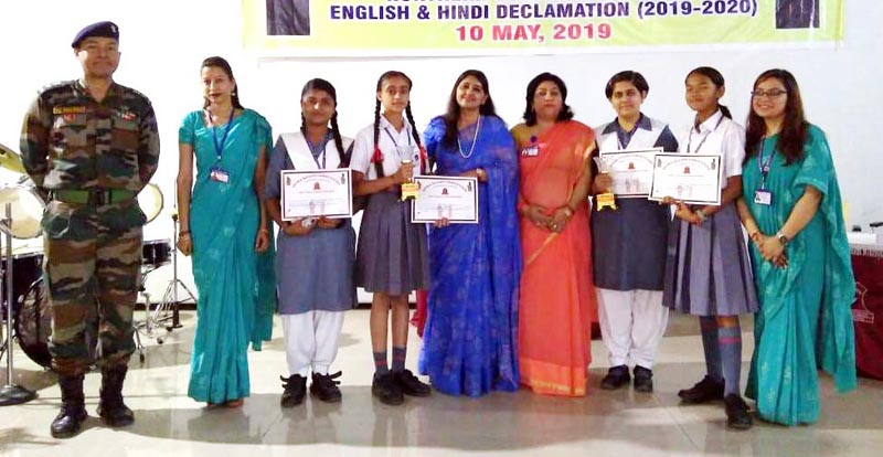 Winners of Declamation Competition posing along with dignitaries at APS Dhar Road in Udhampur.