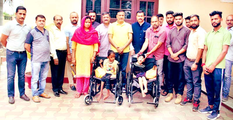 Senior BJP leader and former Minister, Sham Lal Sharma distributing wheelchairs among differently abled students in Raipur Domana on Thursday.