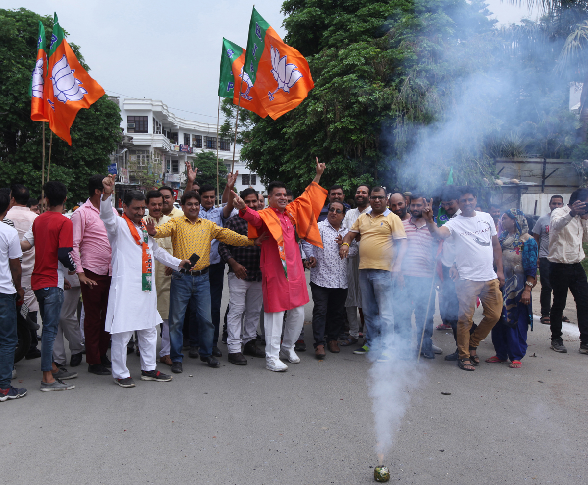 J&K BJP chief Ravinder Raina and other leaders celebrating party's victory by bursting crackers and dancing outside party headquarters at Trikuta Nagar in Jammu on Thursday. — Excelsior/Rakesh