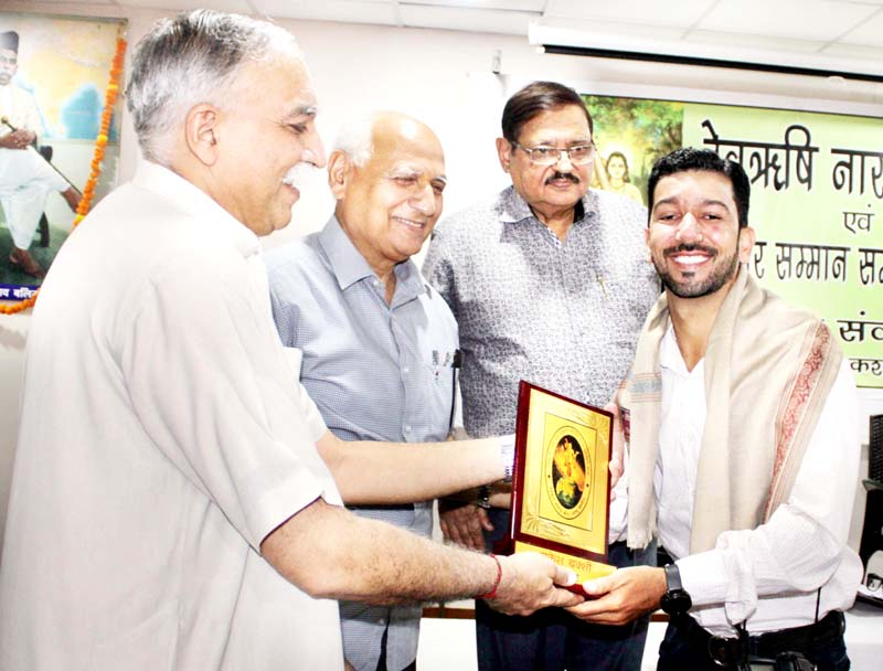 Daily Excelsior photographer, Rakesh Bakshi being presented an award of excellence during celebration of Narad Jayanti at Jammu on Sunday.