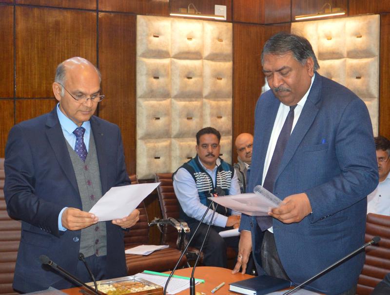 Advisor K K Sharma administering oath to Lokesh Dutt Jha as JKSERC Chairman on Thursday.