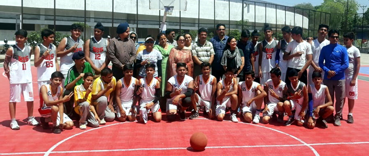 Participating teams posing with DYSSO Jammu, Chanchal Kour at Basketball court, MA Stadium in Jammu on Thursday.