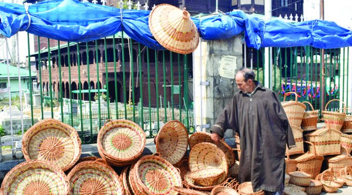 An elderly man selling wicker baskets on a street in Old City, Srinagar. —Excelsior/Shakeel
