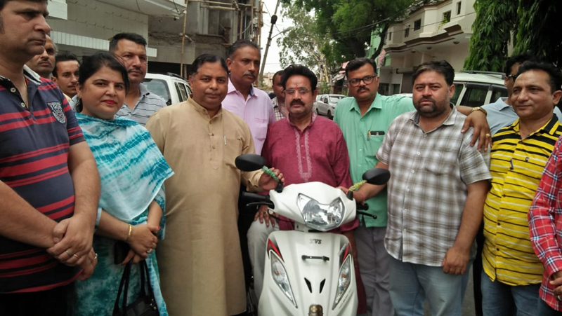 Former Minister, Sat Sharma handing over a scooty to a differently abled person in Jammu on Tuesday.