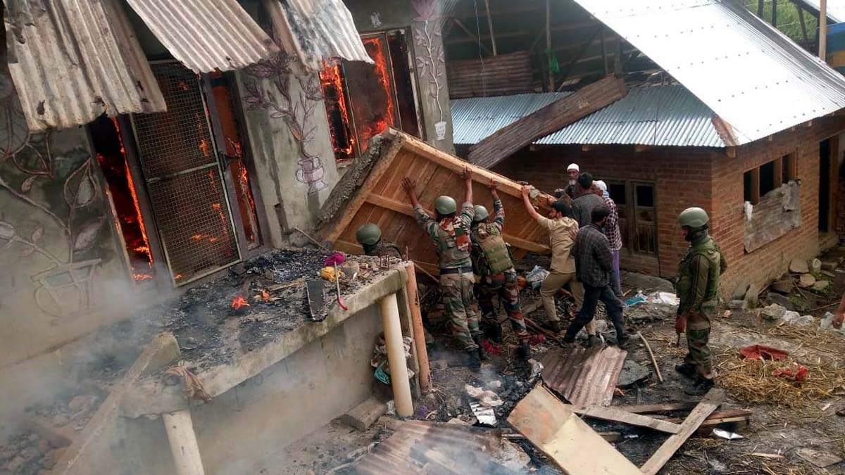 Armymen salvaging household items during fire in a house at Ganai Mohalla, Dudbug, Baramulla.