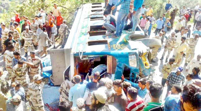 Locals and police rescuing passengers from ill-fated bus in district Doda on Friday.
