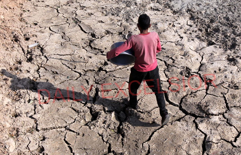 A boy crosses dried pond on a hot summer day on the outskirts of Jammu on Wednesday. —Excelsior/Rakesh