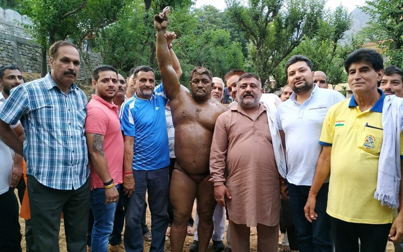 Winner of 2nd Annual Arli (Katra) Dangal title poses with chief guest at Arli in district Reasi.