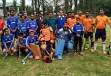 Players posing during a match of Anantnag Hockey League Tournament on Monday.