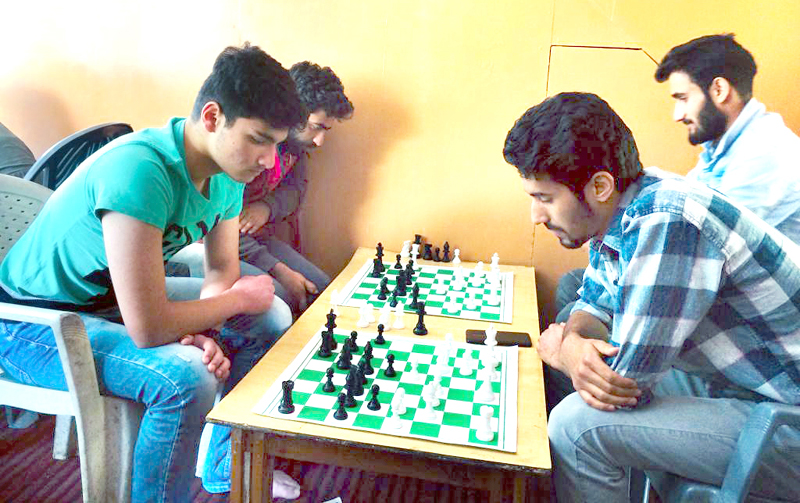 Players showing keen interest during a Chess game in Srinagar.