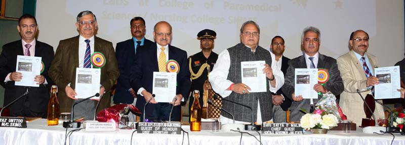 Governor Satya Pal Malik flanked by others releasing publication of SKIMS during a function in Srinagar on Wednesday.