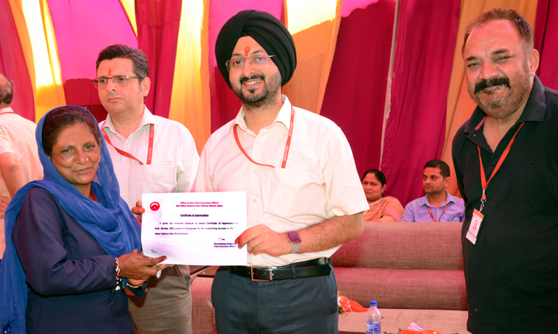 CEO Shrine Board Simrandeep Singh giving certificate to one of the employees at Katra on Tuesday.