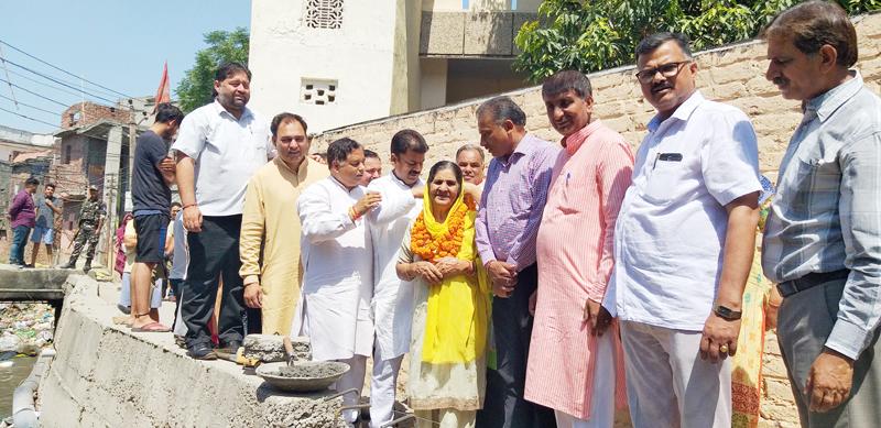 Former Minister, Sat Sharma kick starting construction work of nallah at Shakti Nagar on Wednesday.