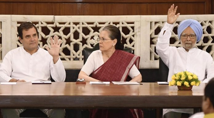 Congress president Rahul Gandhi and former Prime Minister Manmohan Singh raise their hands to elect Sonia Gandhi as Congress Parliamentary Party leader at Central Hall of Parliament in New Delhi on Saturday. (UNI)