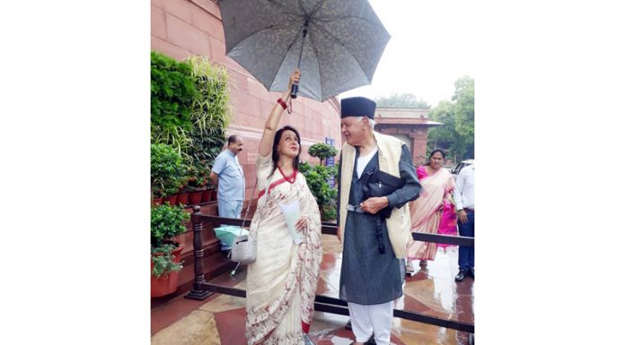 BJP Lok Sabha MP Hema Malini and NC president Dr Farooq Abdullah take cover from rain outside Parliament House on Thursday.