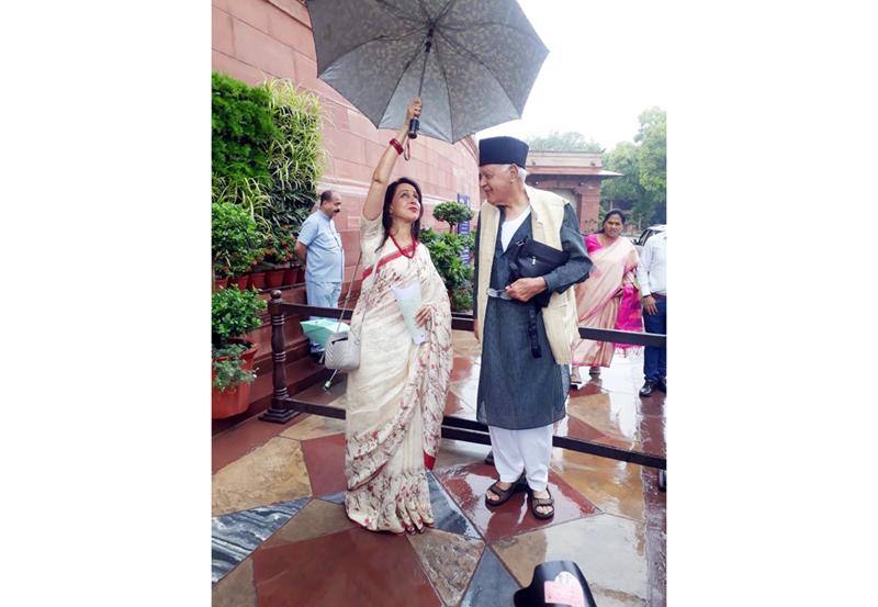 BJP Lok Sabha MP Hema Malini and NC president Dr Farooq Abdullah take cover from rain outside Parliament House on Thursday.