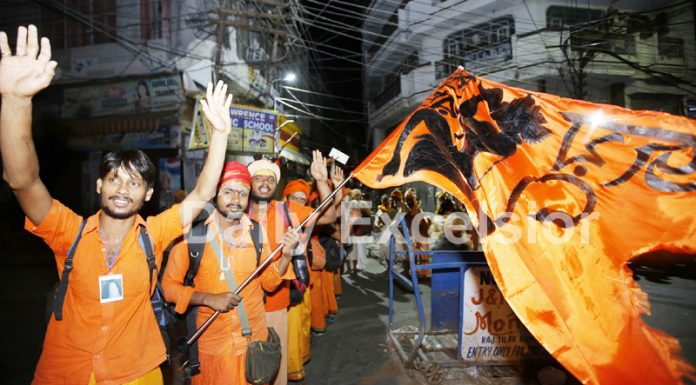 Jubilant Amarnathji yatris displaying a religious flag before leaving for holy cave from Jammu on Saturday. -Excelsior/Rakesh
