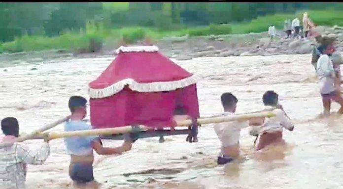 Baratis carrying bride cross flooded Nullah in Breri village of Billawar tehsil in Kathua district on Friday. Reports said there was a sudden flood in Nullah due to heavy rains.