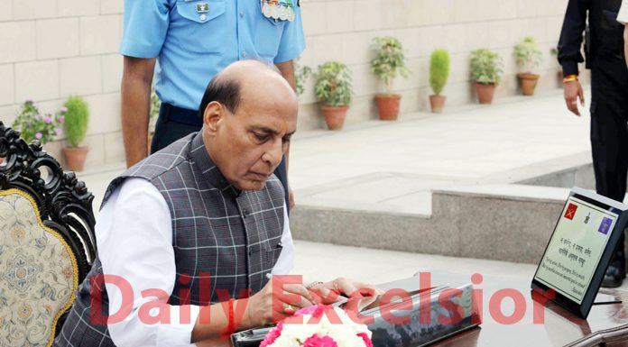 Defence Minister Rajnath Singh signing the visitors' book after paying homage to martyrs on the occasion of the 20th anniversary of Kargil Vijay Diwas at the National War Memorial in New Delhi on Friday.