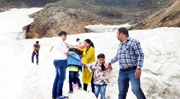 Tourists enjoy snow at Padri meadow in Bhaderwah. There has been influx of tourists at Padri during past few days. -Excelsior/Tilak Raj