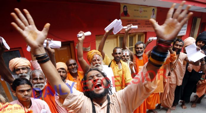 Sadhus singing bhajans and dancing in front of a registration counter at Jammu on Monday. -Excelsior/Rakesh