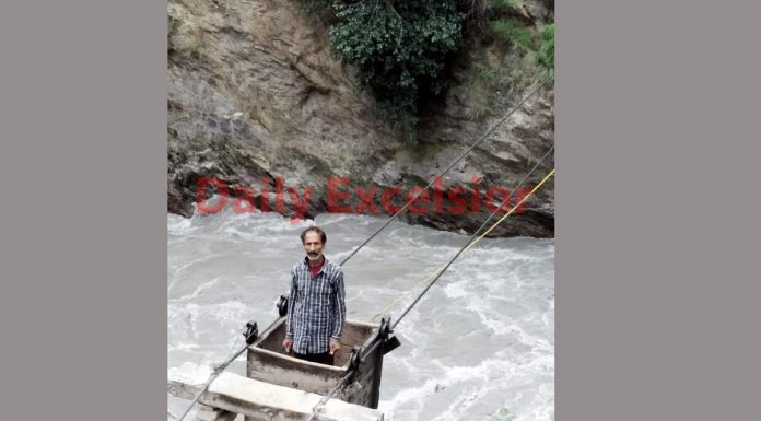 A man of Kontwara area in Kishtwar district crossing the river in a trolley due to failure of Government to construct the bridge.