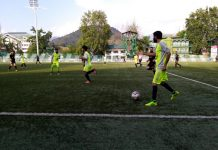 Footballers in action during a match of State Football League Tournament in Srinagar.