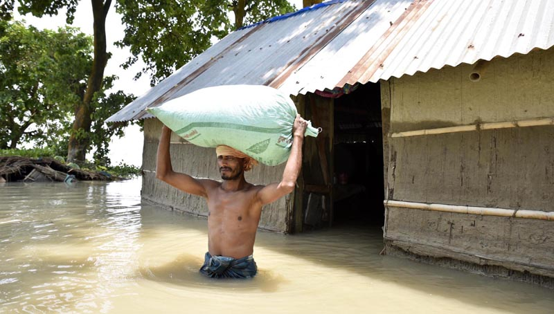 A villager with belonging leaving his submergbed house for a safer location, in Morogaon on Saturday. (UNI)
